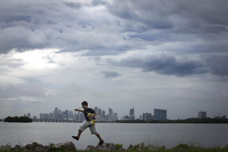 A boy jumps on rocks as he plays along a causeway on a rainy day with the city skyline in background in Miami, July 21, 2014. REUTERS/Carlo Allegri (UNITED STATES - Tags: SOCIETY CITYSCAPE)