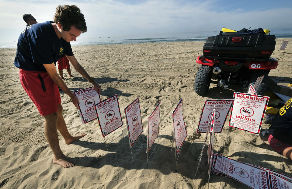 Lifeguards gather signs to post that warn that water contact may cause illness as they close the beach after an oil spill in Huntington Beach, Calif., Sunday, Oct. 3, 2021. (AP Photo/Ringo H.W. Chiu)