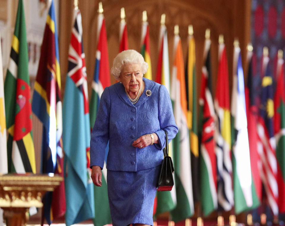 Britain's Queen Elizabeth II walks past Commonwealth flags in St George's Hall at Windsor Castle, England to mark Commonwealth Day in this image that was issued on Saturday March 6, 2021. The timing couldn't be worse for the Queen's grandson Harry and his wife Meghan. The Duke and Duchess of Sussex will finally get the chance to tell the story behind their departure from royal duties directly to the public on Sunday, when their two-hour interview with Oprah Winfrey is broadcast. (Steve Parsons/Pool via AP)