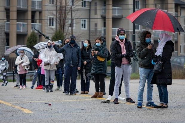 People line up in the rain outside a temporary COVID-19 vaccine clinic at the Warden Hilltop Community Center in Scarborough on April 28, 2021. (Evan Mitsui/CBC - image credit)