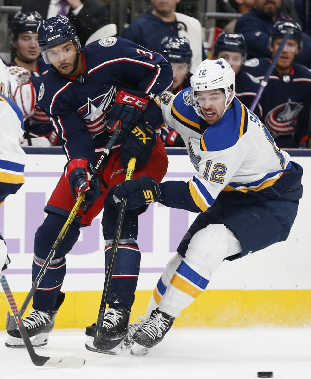 Columbus Blue Jackets' Seth Jones, left, passes the puck in front of St. Louis Blues' Zach Sanford during the second period of an NHL hockey game Friday, Nov. 15, 2019, in Columbus, Ohio. (AP Photo/Jay LaPrete)
