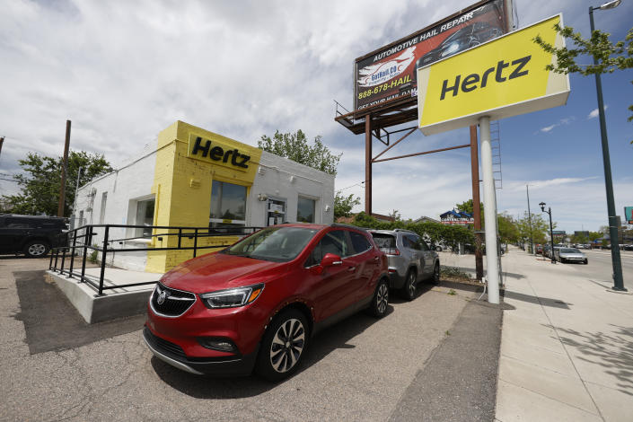 Rental vehicles are parked outside a closed Hertz car rental office Saturday, May 23, 2020, in south Denver. (AP Photo/David Zalubowski)