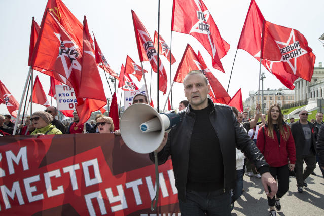 <p>Russian opposition activist Sergey Udaltsov, foreground, leads a group of his supporters during a Communist rally to mark May Day in Moscow, Russia, May 1, 2018. More than 100,000 people came out on the streets on Moscow to march in the traditional May Day parade. The banner behind him reads 'Communism instead of Putin'. (Photo: Alexander Zemlianichenko/AP) </p>