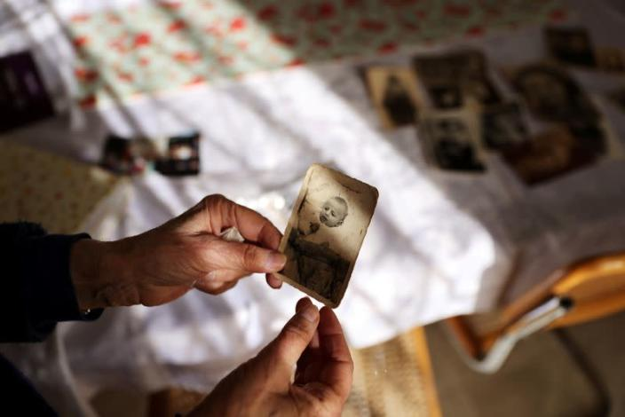 Holocaust survivor Leah Nebenzahl holds a photograph of herself as a baby during her interview with Reuters in Jerusalem