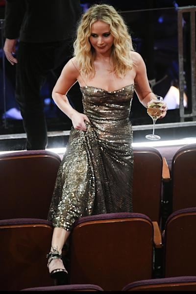 Jennifer Lawrence Climbs Over Seats At The Oscars With Wine In Hand