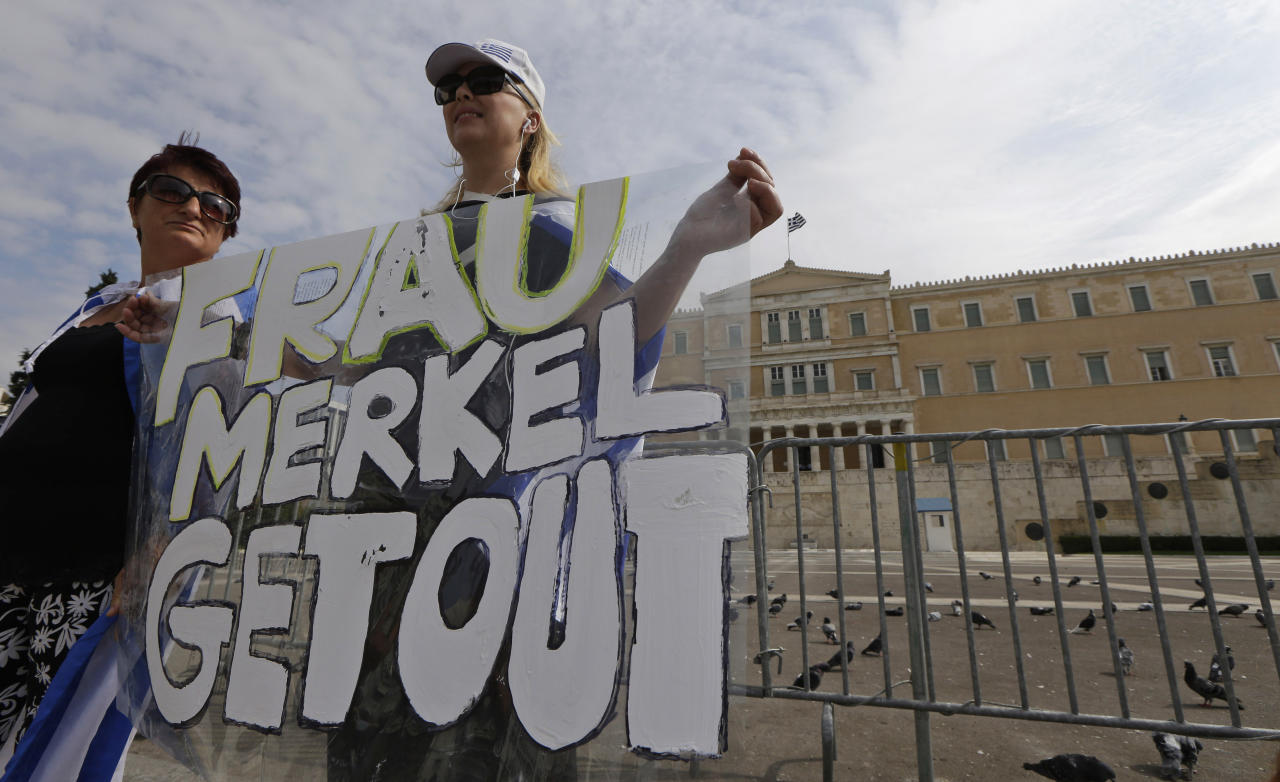 Demonstrator holds an anti-Merkel banner prior to a protest in front of the Greek Parliament in Athens on Tuesday Oct. 9, 2012. German Chancellor Angela Merkel makes her first visit to Greece since the eurozone crisis began three years ago. Her five-hour stop is seen by the government as a historic boost for the country's future in Europe's shared currency, but by protesters as a harbinger of more austerity and hardship. More than 7,000 police will be on hand, cordoning off parks and other sections of central Athens, to keep demonstrators away from the German leader who is due to arrive Tuesday in the Greek capital for talks with conservative Prime Minister Antonis Samaras. (AP Photo/Lefteris Pitarakis)