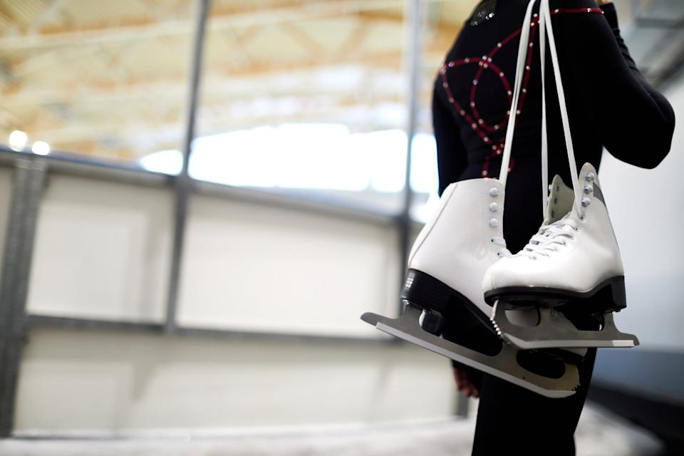 Closeup of unrecognizable girl holding figure skates over shoulder leaving ice rink after sports training, copy space