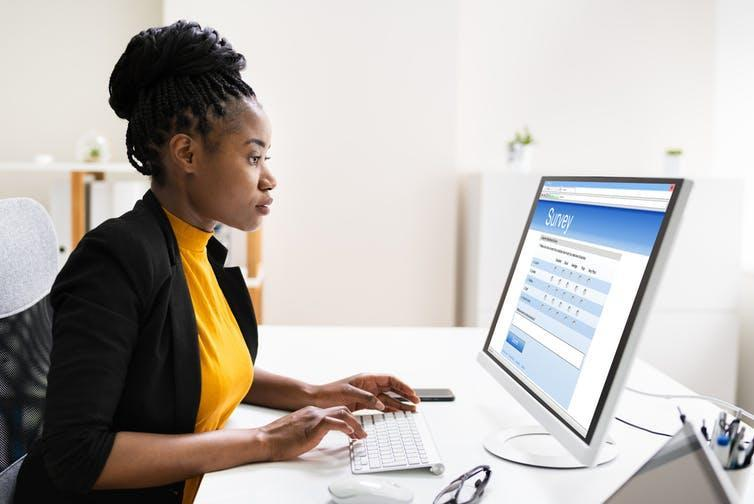 Black business woman fills out survey on computer