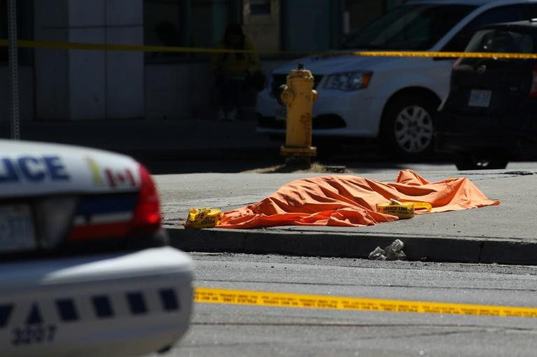 An unidentified body is seen near the crime scene after a truck hit several pedestrians in Toronto