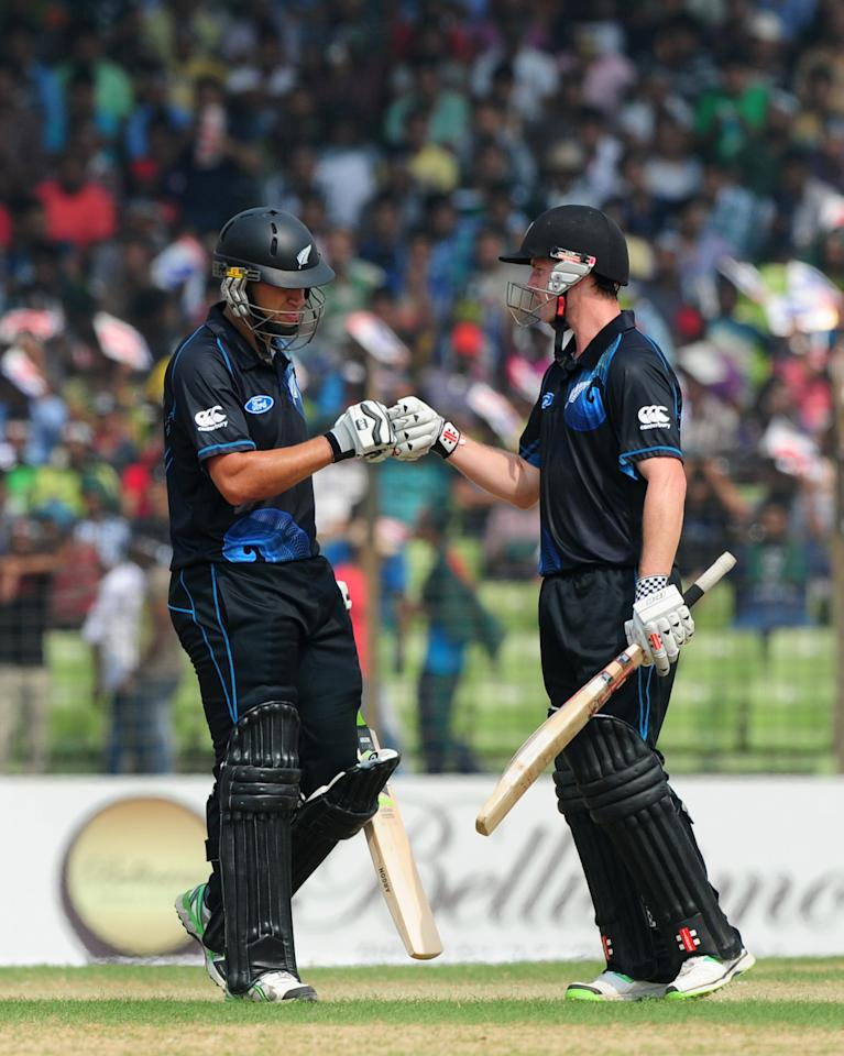 New Zealand batsman Ross Taylor (L) celebrates with his teammate Colin Munro after hitting a boundary during the third One-Day International (ODI) cricket match between Bangladesh and New Zealand at Khan Jahan Ali Stadium in Fatullah, on the outskirts of Dhaka on November 3, 2013.  AFP PHOTO/ Munir uz ZAMAN        (Photo credit should read MUNIR UZ ZAMAN/AFP/Getty Images)