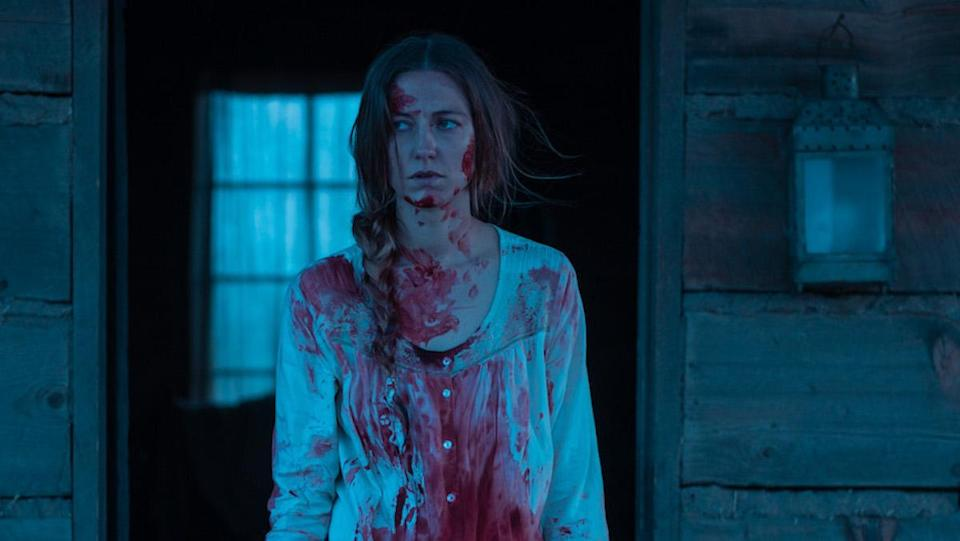 Lizzy Macklin, covered in blood, stands in front of her house in The Wind