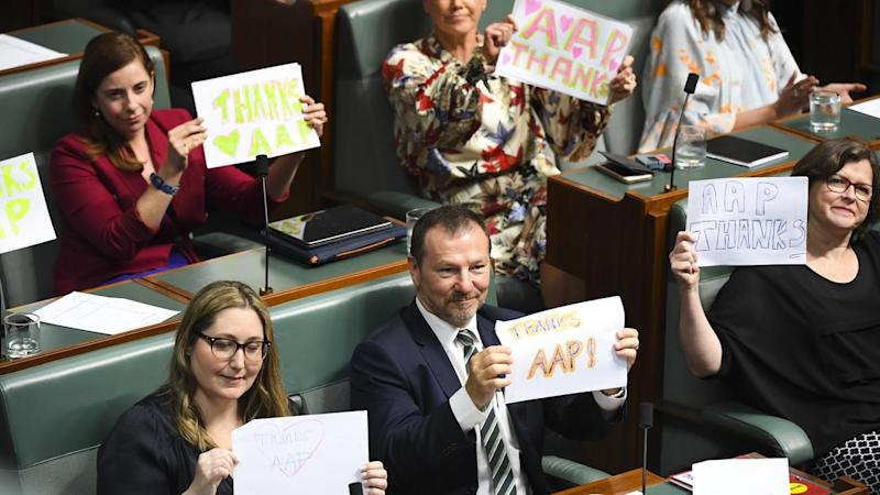 "In federal parliament Labor MPs held up signs which read ""thank you AAP"""