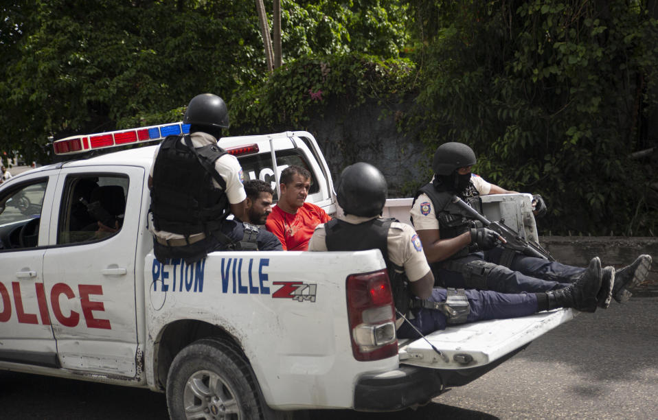The police take two detainees to the police station of Petion Ville in Port-au-Prince, Haiti, Thursday, July 8, 2021. According to Police Chief Leon Charles, the two detained are suspects in the assassination of Haitian President Jovenel Moïse. (AP Photo/Joseph Odelyn)