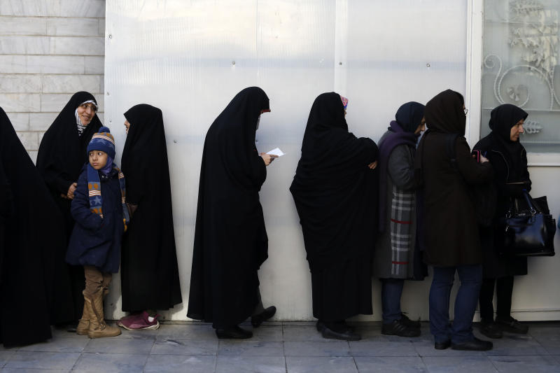 Iranians queue for voting in the parliamentary elections in a polling station in Tehran, Iran, Friday, Feb. 21, 2020. Iranians began voting for a new parliament Friday, with turnout seen as a key measure of support for Iran's leadership as sanctions weigh on the economy and isolate the country diplomatically. (AP Photo/Vahid Salemi)