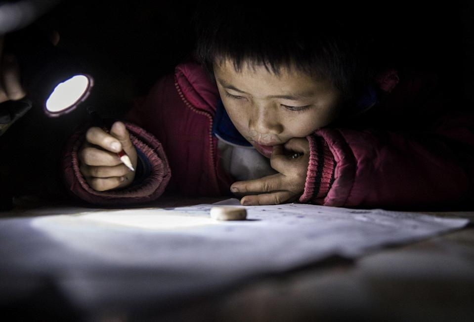 A child does his homework by flashlight at his family's home in Anshun, China. Photo: Getty Images