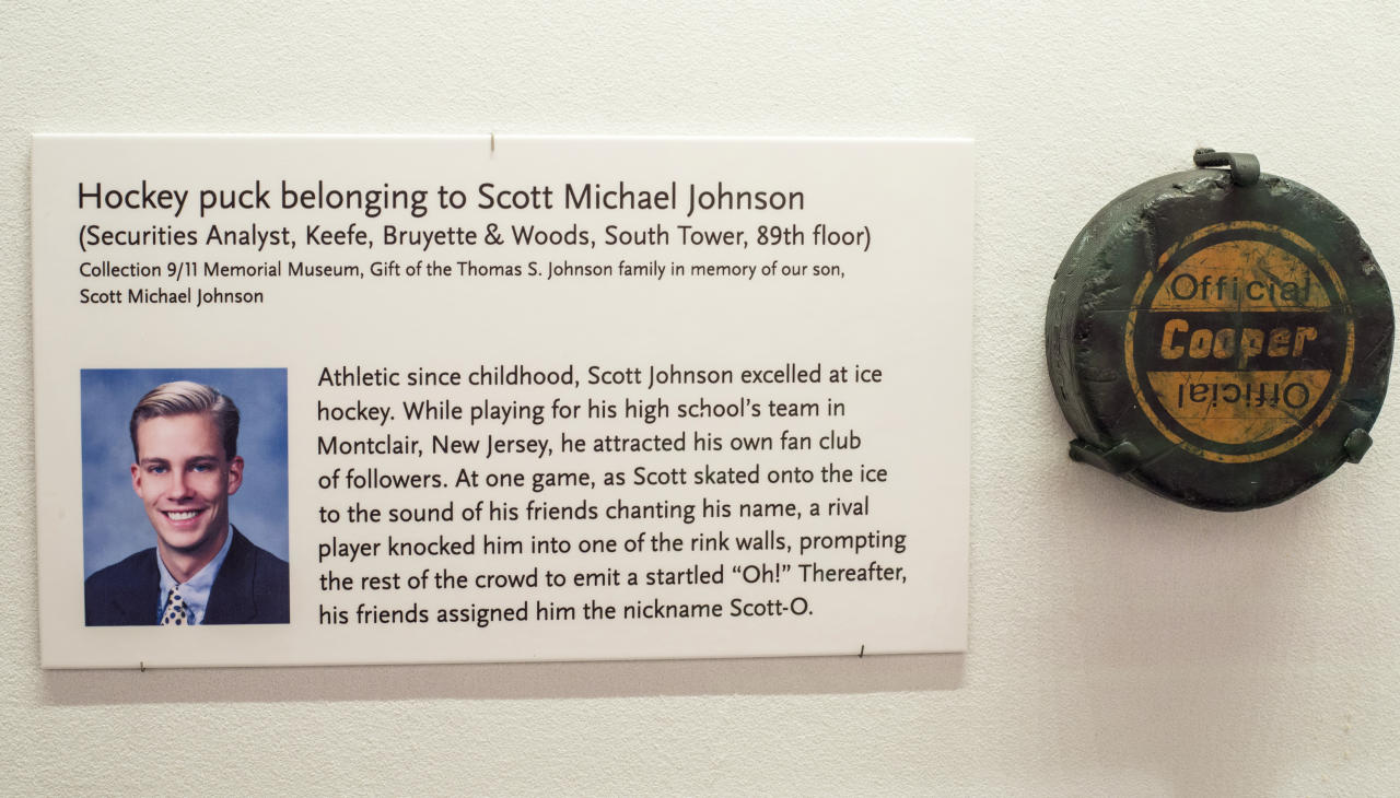 This 2015 photo provided by the National September 11 Memorial & Museum shows a photo of Scott Michael Johnson in a display at the museum in New York. The display included a photo and a hockey puck that were a gift of the Thomas S. Johnson family in memory of their son, who died at the World Trade Center in the Sept. 11 attacks. The remains of the 26-year-old securities analyst, an employee at the investment banking company Keefe, Bruyette & Woods at the World Trade Center, was identified Wednesday, July 25, 2018, nearly 17 years after the attacks. (Jin Lee/National September 11 Memorial & Museum via AP)