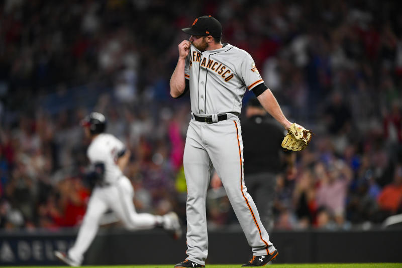 San Francisco Giants pitcher Sam Coonrod wipes his face as Atlanta Braves' Adam Duvall rounds first base during his two-run home run to left center field in the seventh inning of a baseball game, Saturday, Sept. 21, 2019, in Atlanta. (AP Photo/John Amis)