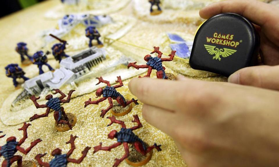 A customer uses a tape measure to play Warhammer in a London Games Workshop store in London.