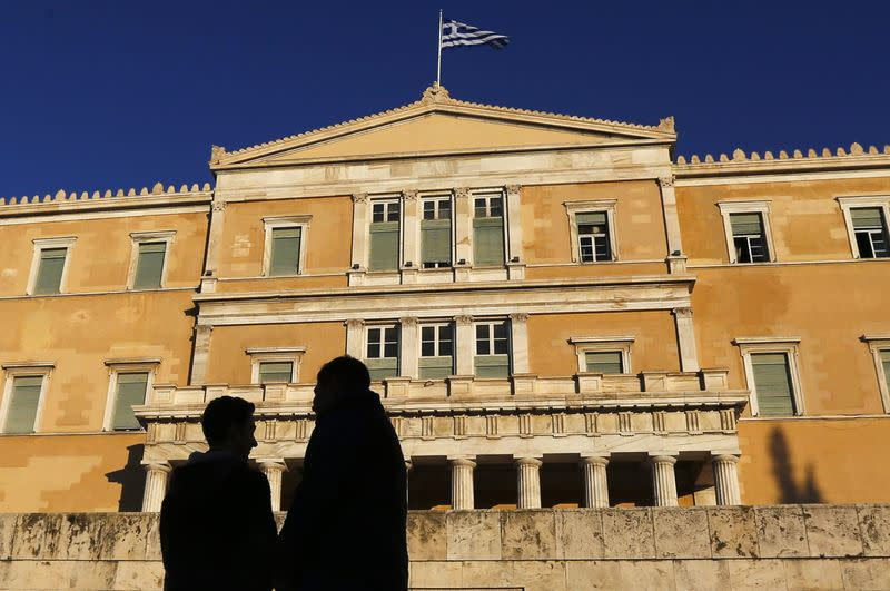 People are silhouetted as they gather ahead of an anti-austerity and pro-government demonstration in front of the parliament in Athens