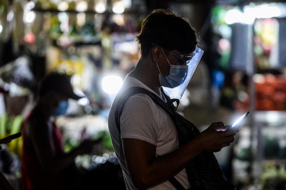 FILE PHOTO: A man wearing a face mask and a face shield uses his smartphone at a bus terminal in Quezon City, Philippines on August 22, 2020. (Photo by Lisa Marie David/NurPhoto via Getty Images)