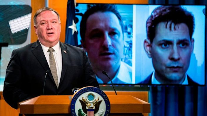 Michael Spavor and Michael Kovrig are shown on a video monitor as US Secretary of State Mike Pompeo, speaks during a news conference in July