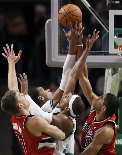 Boston Celtics Jared Sullinger, center left, and Paul Pierce, center right, vie for a rebound with Portland Trail Blazers' Meyers Leonard, left, and Nicolas Batum, right, in the first quarter of an NBA basketball game in Boston, Friday, Nov. 30, 2012. (AP Photo/Michael Dwyer)