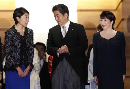 Japan's Prime Minister Shinzo Abe (C) talks with Economy, Trade and Industry Minister Yuko Obuchi (L) and Internal Affairs and Communications Minister Sanae Takaichi as they prepare for a photo session at his official residence in Tokyo September 3, 2014. REUTERS/Toru Hanai