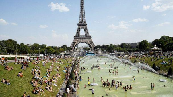 PHOTO:People cool off and sunbathe by the Trocadero Fountains next to the Eiffel Tower in Paris, on July 25, 2019 as a new heatwave hits the French capital. (Bertrand Guay/AFP/Getty Images)