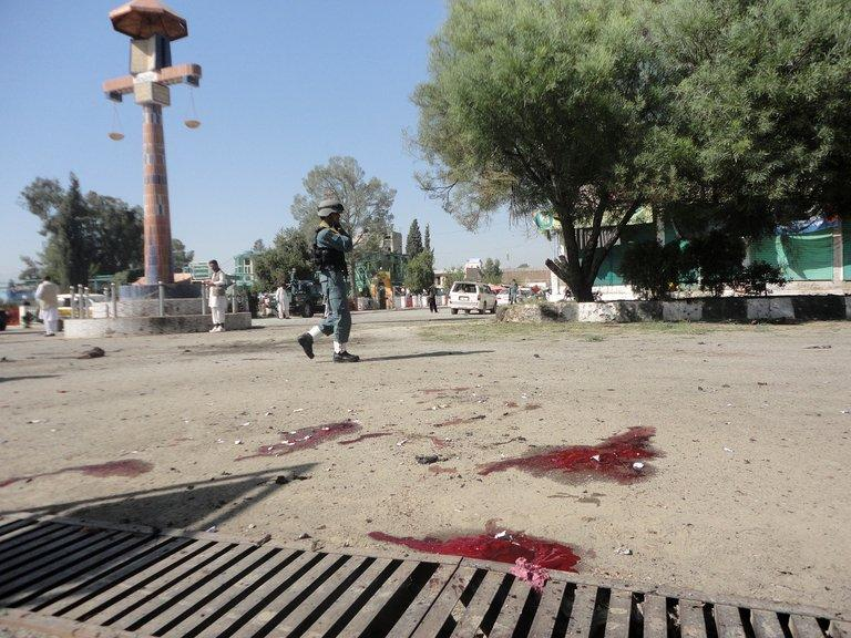 An Afghan policeman walks past the site of a bomb attack in Khost on October 1, 2012