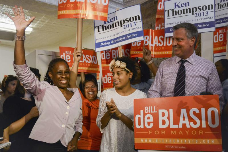 Chirlane McCray, the wife of New York mayoral candidate Bill de Blasio (R), waves after being introduced while attending a campaign rally with their daughter Chiara (C) in Brooklyn, New York