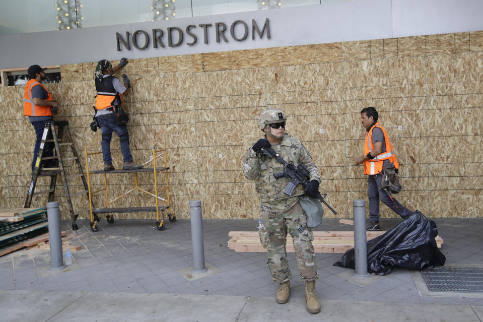 A member of the National Guard stands in front of a Nordstrom store as it is boarded up Monday, June 1, 2020, in Santa Monica, Calif., a day after unrest and protests over the death of George Floyd, a black man who died in police custody in Minneapolis on May 25. (AP Photo/Marcio Jose Sanchez)