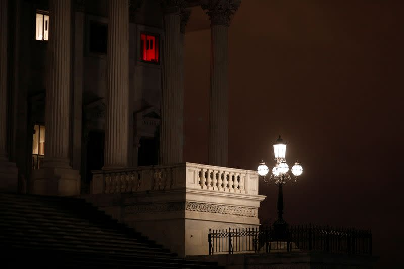 A window illuminated with a red light shines above the U.S. Senate steps, ahead of a vote on the coronavirus (COVID-19) relief bill on Capitol Hill in Washington