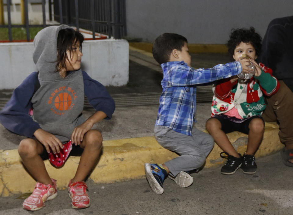 Children wait for their group to be ready to leave San Pedro Sula, Honduras by foot before dawn Tuesday, March 30, 2021. The migrant group aims to reach the U.S. (AP Photo/Delmer Martinez)