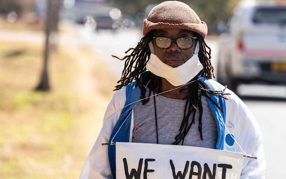 Zimbabwean novelist Tsitsi Dangarembga holds a placard during an anti-corruption protest march along Borrowdale road, on July 31, 2020 in Harare - AFP