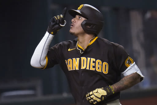 San Diego Padres' Manny Machado points upward while rounding the bases on his solo home run off Los Angeles Dodgers' Clayton Kershaw during the sixth inning in Game 2 of a baseball National League Division Series Wednesday, Oct. 7, 2020, in Arlington, Texas. (AP Photo/Sue Ogrocki)