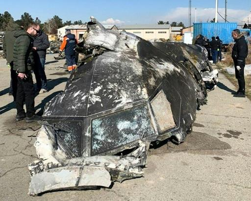 People analyze the fragments and remains of the Ukraine International Airlines plane that crashed outside Tehran