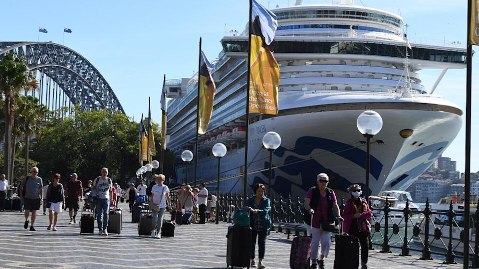 Passengers are seen disembarking the Ruby Princess cruise in Sydney on Thursday.