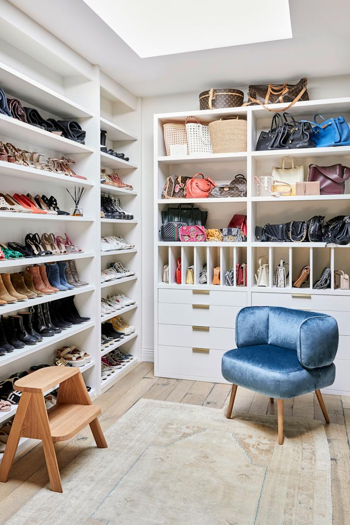 """<div class=""""caption""""> """"I don't ever have enough time to get ready, so it was important to have a closet with a natural organization element. Bags here, tees here,"""" says Duff. """"But my closet <em>never</em> looks this organized. Normally, that chair is covered in clothes, and I can't even see how pretty it is."""" The seat in question: a Parker chair by <a href=""""https://www.interiordefine.com/"""" rel=""""nofollow noopener"""" target=""""_blank"""" data-ylk=""""slk:Interior Define"""" class=""""link rapid-noclick-resp"""">Interior Define</a>, in sapphire and white oak. </div>"""