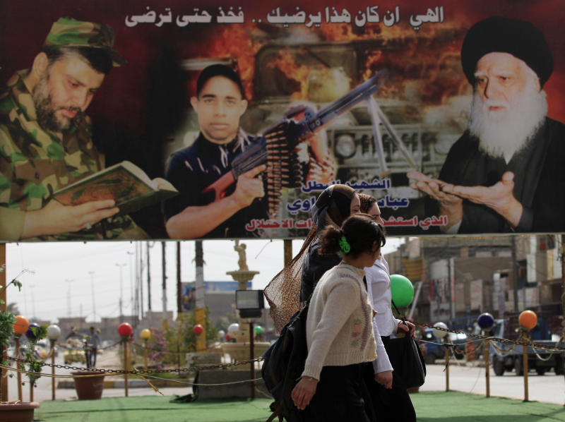 """In this Sunday, Feb. 24, 2013 photo, women walk past a poster of Shiite religious leaders and a Shiite fighter killed during a fight between US troops and al-Mahdi Army militia in the Jihad neighborhood of west Baghdad, Iraq. Fliers claiming to be from a new Iranian-linked Shiite militant group began turning up last week in front of Iraqi Sunni households bearing a chilling message: Get out now or face """"great agony"""" soon. Their reemergence now, nearly a decade after the U.S.-led invasion, is a worrying sign that rising sectarian tensions are again gnawing away at Iraqi society and could undo fragile gains made in recent years. (AP Photo/ Karim Kadim)"""