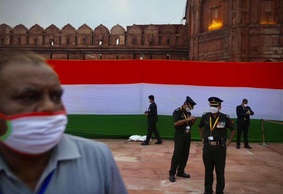 Security personnel wearing face masks wait for the start of the Independence Day ceremony on the ramparts of the landmark Red fort monument in New Delhi, India, Saturday, Aug. 15, 2020. India's coronavirus death toll overtook Britain's to become the fourth-highest in the world with another single-day record increase in cases Friday. (AP Photo/Manish Swarup)