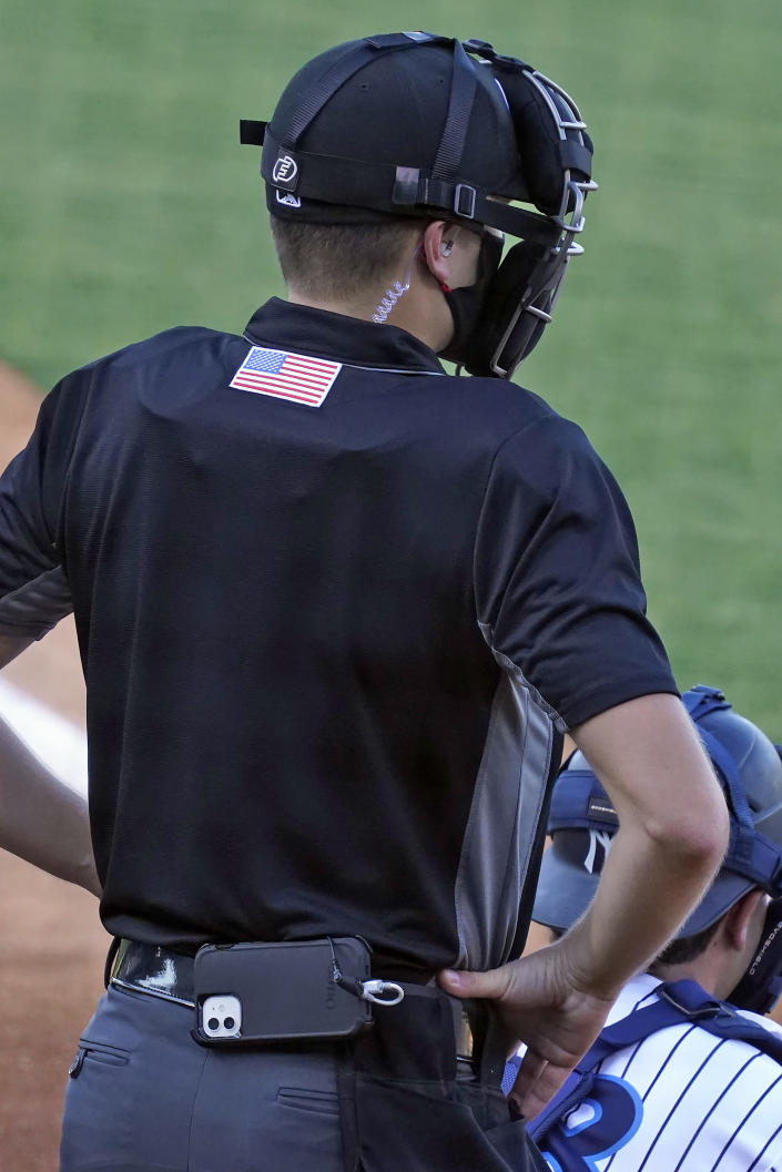 Home plate umpire Kaleb Devier wears an earpiece and a battery pack during a Low A Southeast League baseball game between the Dunedin Blue Jays and the Tampa Tarpons at George M. Steinbrenner Field Tuesday, May 4, 2021, in Tampa, Fla. The game is one of the first in the league to use automatic balls and strike calls. (AP Photo/Chris O'Meara)