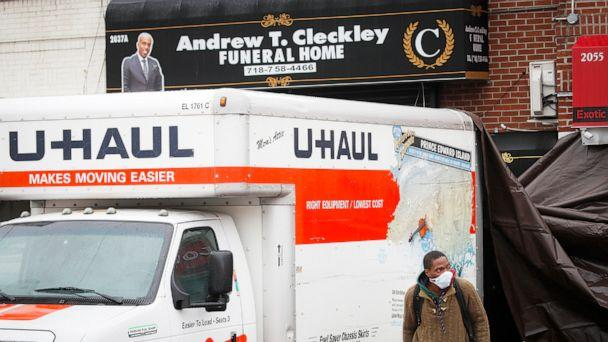 PHOTO: A worker appears from under a tarp covering the back-end of a rental truck outside Andrew T. Cleckley Funeral Home in Brooklyn, New York, April 30, 2020. (John Minchillo/AP)