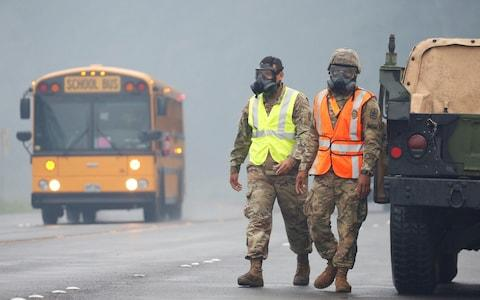 Hawaii National Guard soldiers wear masks to protect themselves from volcanic gases in Pahoa - Credit: Reuters