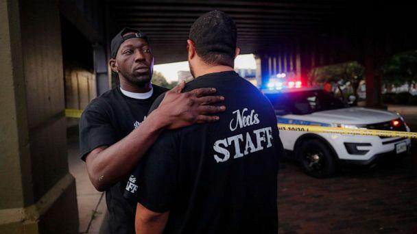 PHOTO: Witnesses comfort one another at the scene of a mass shooting, Sunday, Aug. 4, 2019, in Dayton, Ohio. (John Minchillo/AP)