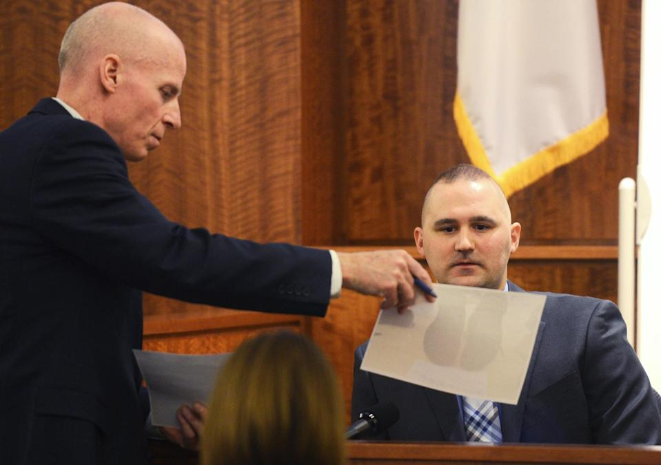 First Assistant District Attorney William McCauley shows a photo to witness North Attleboro police officer Edward Zimmer during the Aaron Hernandez's murder trial at Bristol County Superior Court in Fall River, Massachusetts February 11, 2015. REUTERS/Ted Fitzgerald/Pool (UNITED STATES - Tags: CRIME LAW SPORT FOOTBALL)