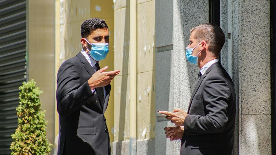 Madrid / Spain - 07 23 20: Two business men outside and wearing a face mask on the streets during Covid-19 pandemic.