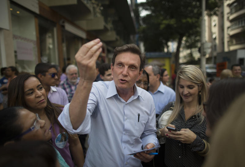 ADDS THAT CRIVELLA HAS RETIRED FROM HIS POST AS BISHOP - In this Sept. 29, 2014 photo, Marcelo Crivella, bishop of the Universal Church of the Kingdom of God, who was running for governor of Rio de Janeiro state, campaigns at Copacabana, Rio de Janeiro, Brazil. While campaigning last year to be Rio de Janeiro's mayor, Crivella, a Pentecostal pastor from one of Brazil's most powerful evangelical churches, repeatedly argued that his faith would not get in the way of governing the nation's most famous city. Crivella is now retired from his post as bishop and is currently a full time politician. (AP Photo/Leo Correa)