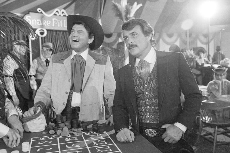 "FILE - In this June 4, 1980, file photo, actors Ross Martin, left, and Robert Conrad, right, are shown while filming a scene of the motion picture ""More Wild, Wild West,"" in Los Angeles. Conrad, the rugged, contentious actor who starred in the hugely popular 1960s television series ""Hawaiian Eye"" and ""The Wild, Wild West,"" has died at age 84. A family spokesperson says the actor died Saturday morning, Feb. 8, 2020, in Malibu, Calif., from heart failure. (AP Photo/Wally Fong, File)"