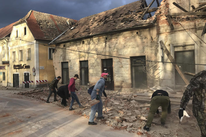 Residents remove debris from a street from a building damaged in an earthquake, in Petrinja, Croatia, Tuesday, Dec. 29, 2020. A strong earthquake has hit central Croatia and caused major damage and at least one death in a town southeast of the capital Zagreb. (AP Photo/Sasa Kavic)