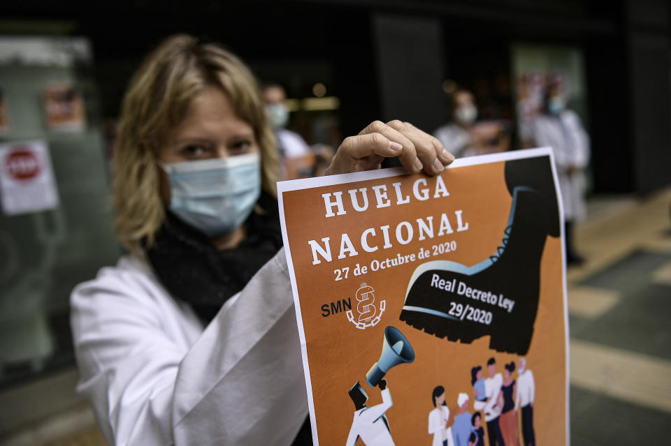 Health service member calling for a general strike and demanding more labor protection on her job, in Pamplona, northern Spain, Tuesday, Oct. 27, 2020, while Spain suffer a second strong pandemic crisis by COVID-19.(AP Photo/Alvaro Barrientos)